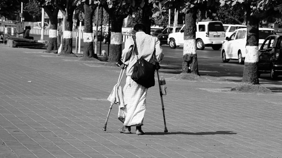 Rear view of disabled man with shoulder bag walking on footpath using crutch in city