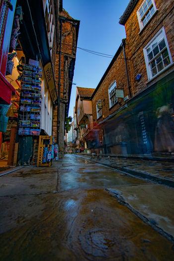 Wet street amidst buildings against sky during rainy season