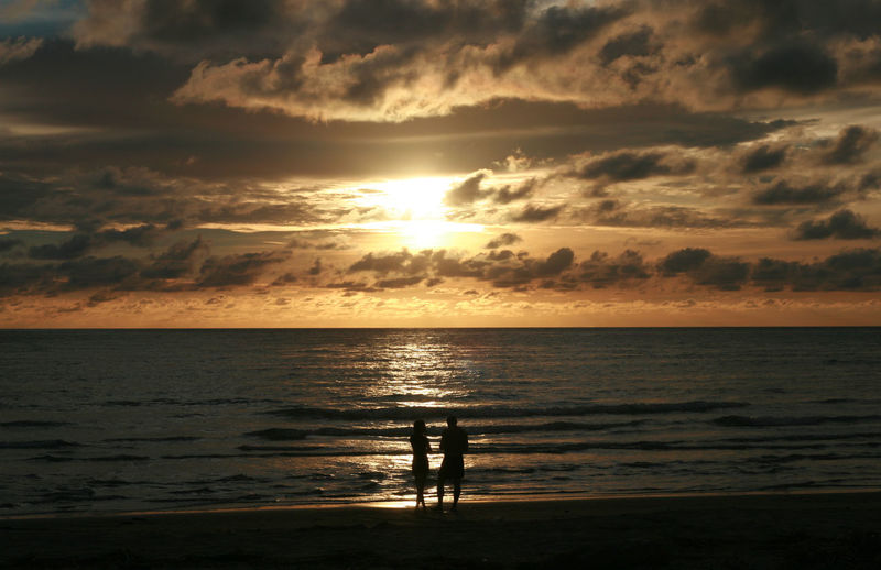 Beach Beauty In Nature Cloud - Sky Day Horizon Over Water Nature Outdoors People Real People Scenics Sea Silhouette Sky Standing Sun Sunlight Sunset Tranquil Scene Tranquility Two People Vacations Water