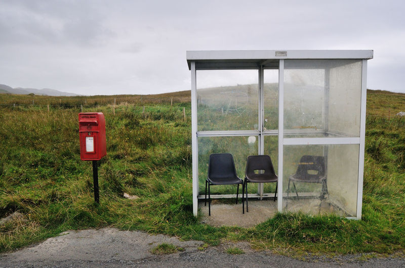 View of old telephone booth on field against sky