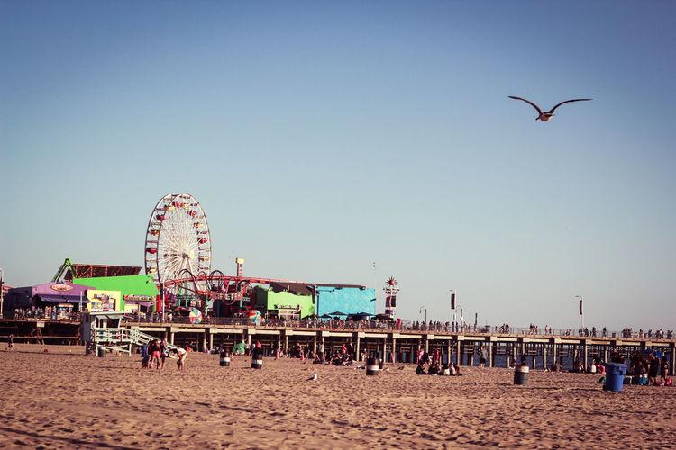 Ferris wheel at beach against clear sky