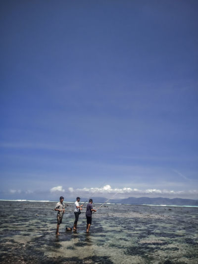 People angling while standing in sea against sky
