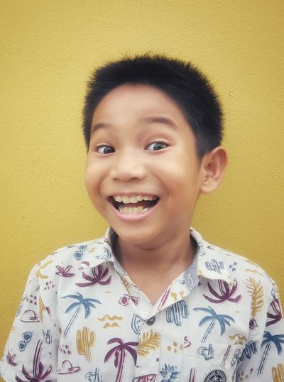 Portrait of smiling boy against yellow wall
