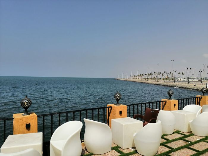 Jazan north sea shore chairs and table by sea against clear sky