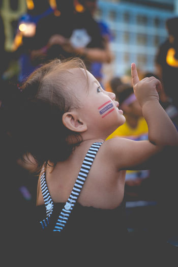 Close-up of cute girl with flag painting on cheek in city