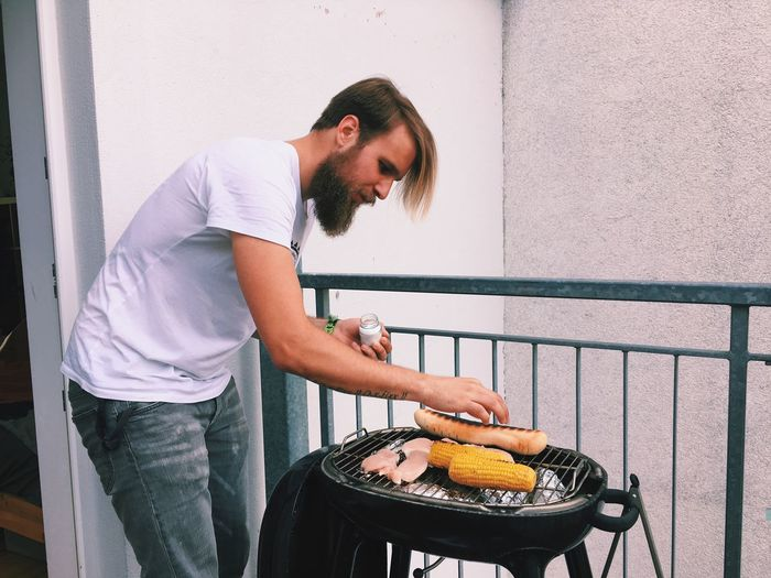 Young Man Cooking Food On Barbecue Grill At Balcony