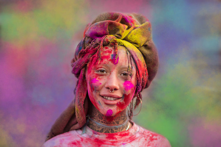 Portrait of smiling young woman with powder paint