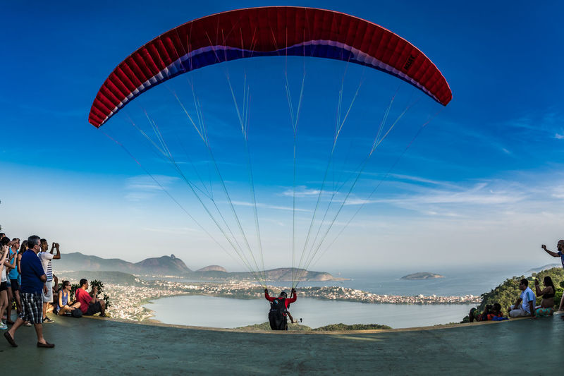 People watching paraglider taking off from mountain peak against sky