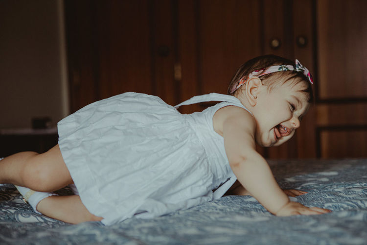Side view of cute baby girl lying on bed at home