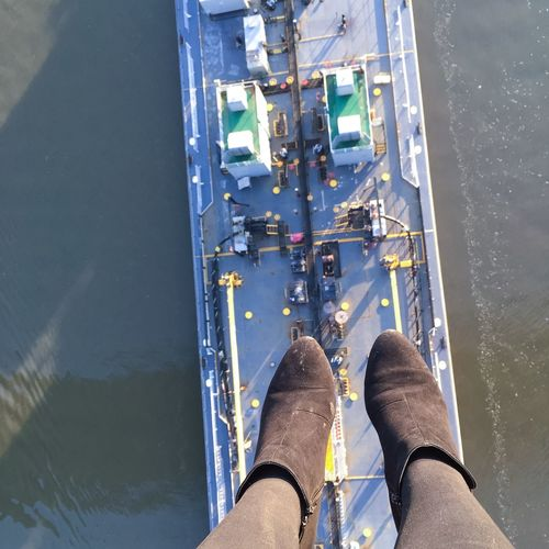 Low Section Of Female Wearing Suede Boots Against Cargo Ship