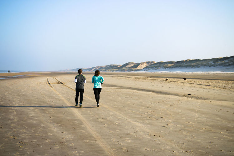 Rear View Of Mother And Son Jogging At Beach