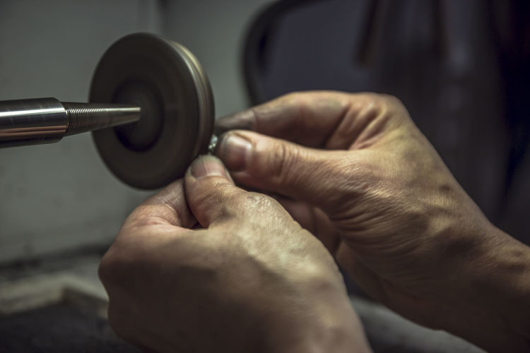 Close-up of hands polishing metal in factory