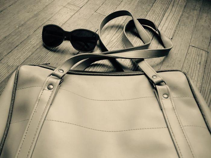 High angle view of purse and sunglasses on hardwood floor