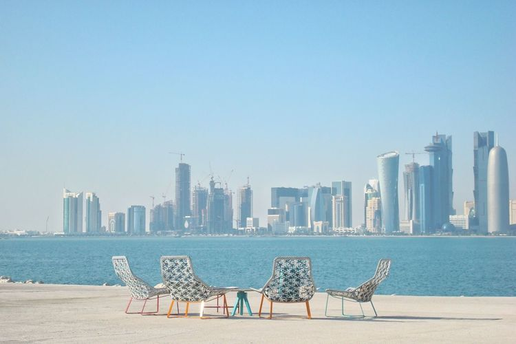 Chairs by sea against buildings in city against clear sky