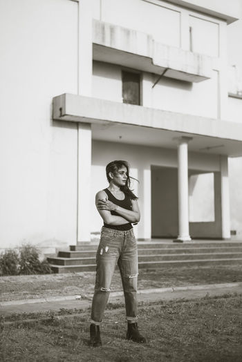 Full length portrait of woman standing on field against building