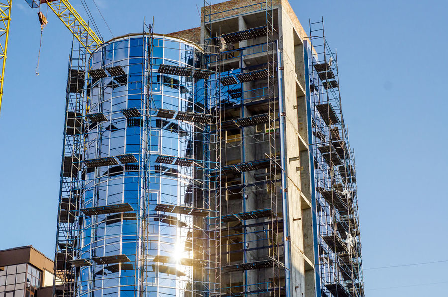 Construction of a semicircular tower in an office building, glazed facade, construction Apartment Architecture Blue Building Building Exterior Built Structure Clear Sky Construction Industry Construction Site Day Development Fire Escape Incomplete Industry Low Angle View Machinery Modern Nature No People Office Building Exterior Outdoors Sky Skyscraper Sunlight