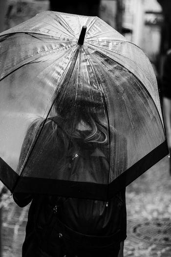 Rear view of woman under umbrella during rainy season