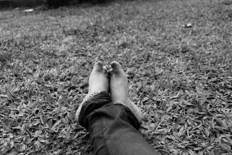 Low section of woman in toe rings relaxing on grassy field