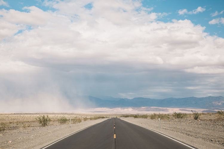 Empty road against cloudy sky at death valley national park