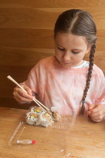 Close-up of girl holding ice cream on table