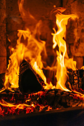 Close-up of fireplace with burning logs of wood. Fire Flame Burning Fire - Natural Phenomenon Heat - Temperature Glowing Wood Wood - Material Log Motion Nature Orange Color Firewood Close-up No People Fireplace Night Bonfire Event Burnt Campfire