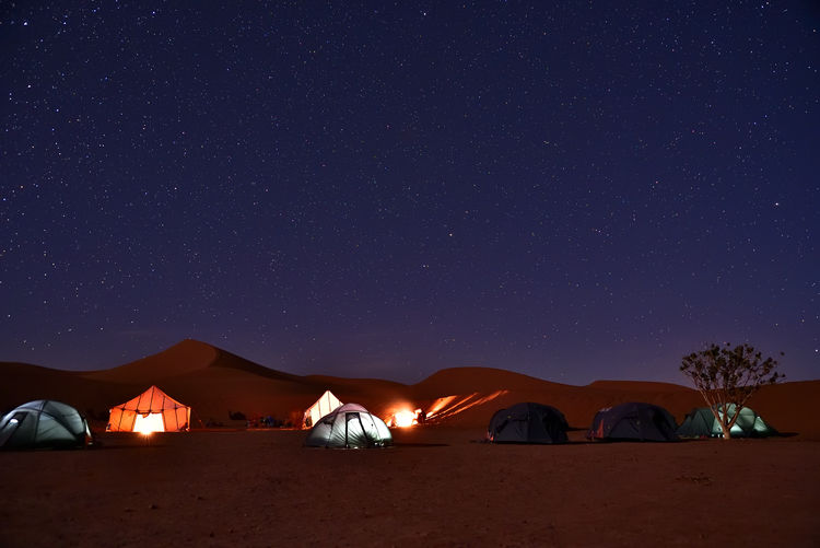Tent on mountain against sky at night