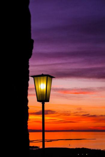 Illuminated gas light against dramatic sky during sunset