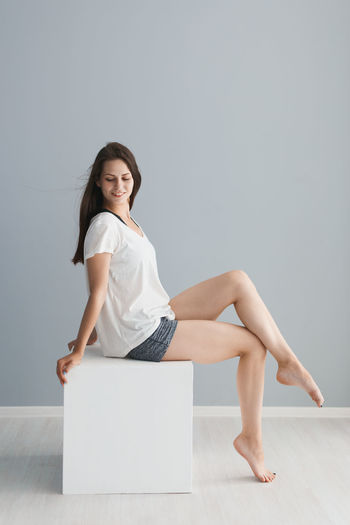 Full length of young woman sitting on white block against gray wall at home