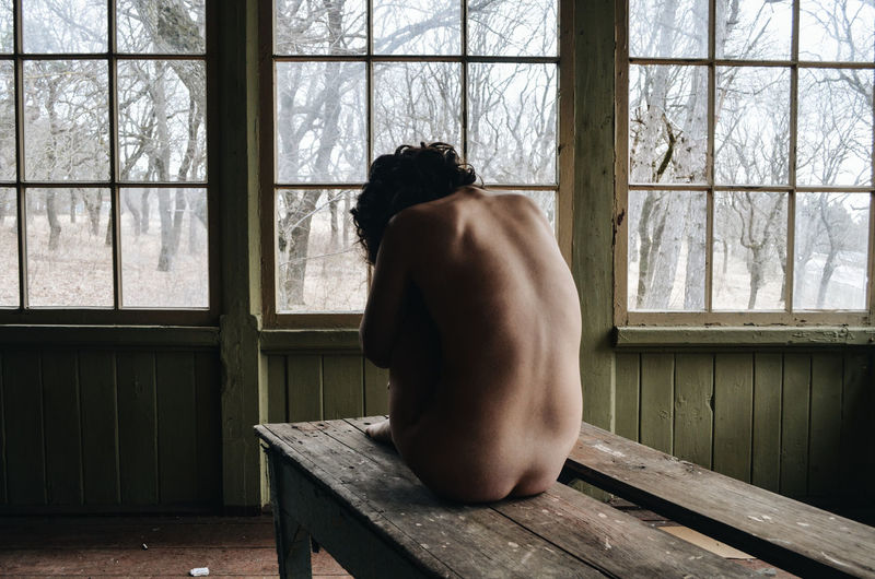 Rear view of shirtless woman sitting on bench in abandoned room