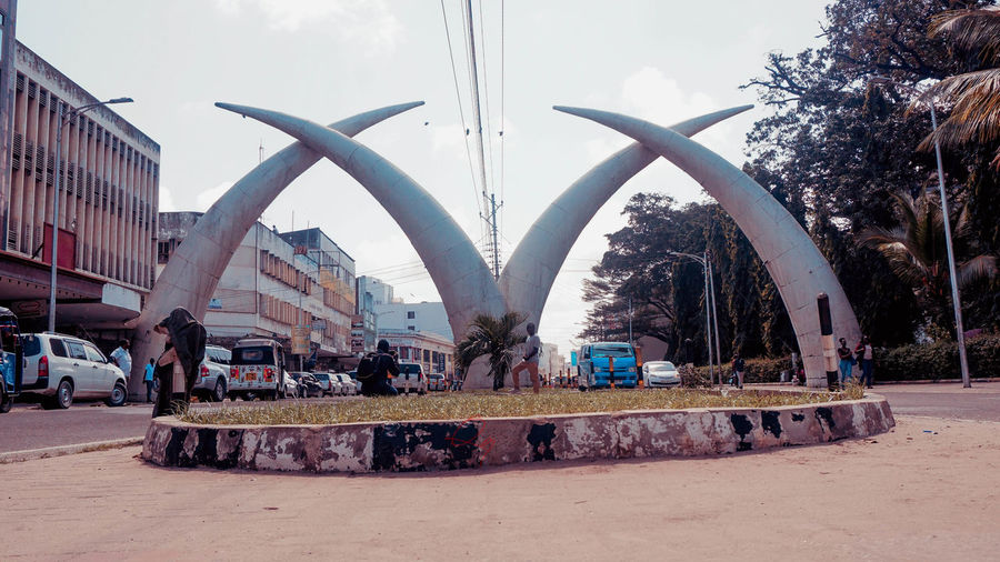 Arch Architecture Building Exterior Built Structure Car City Day Group Of People Incidental People Land Vehicle Mode Of Transportation Mombasa Mombasabeaches Mombasakenya Motor Vehicle Nature Outdoors Plant Real People Sky Street Transportation Travel Tree