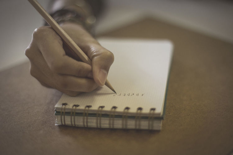 Cropped hand of female student writing on notepad on desk