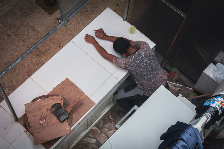 High Angle View Real People One Person Indoors  Lifestyles Full Length Men Women Casual Clothing Day Working Flooring Adult Occupation Directly Above Child Tile Cardboard Messy Tiled Floor