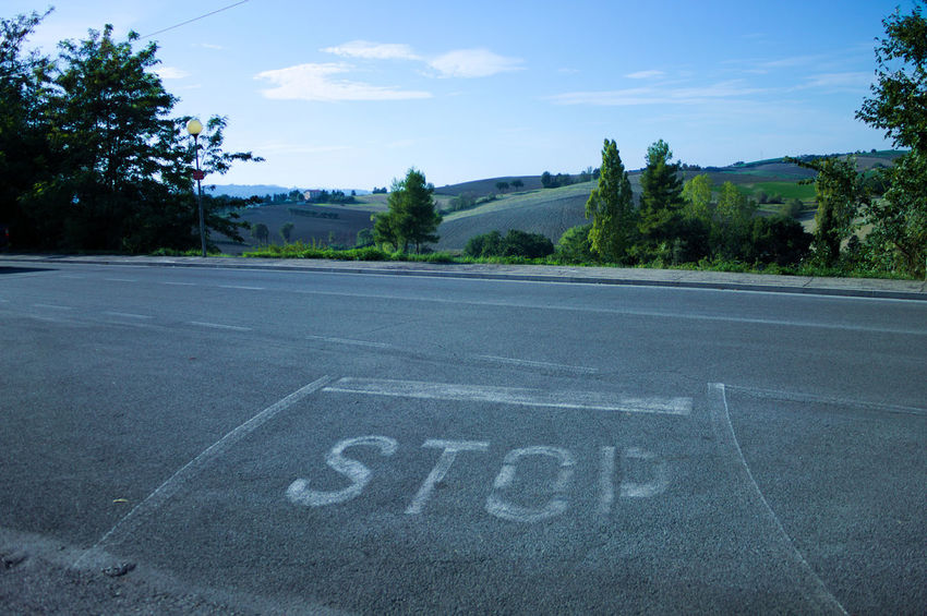 STOP Sky And Clouds The Week On EyeEm Asphalt Blue Close-up Communication Day Landscape Nature No People Outdoors Road Road Marking Sky Stop Stop Line Text Transportation Tree