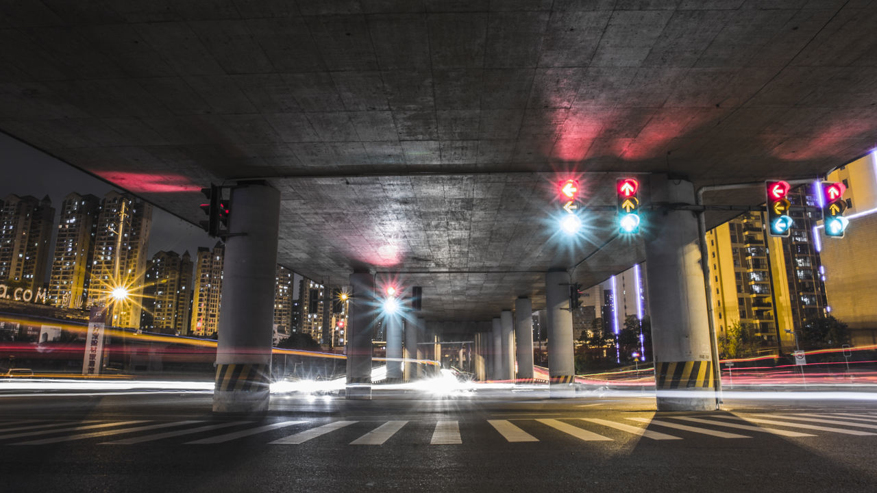 illuminated, architecture, night, built structure, street, transportation, city, road, speed, city life, long exposure, blurred motion, motion, street light, building exterior, outdoors, architectural column, high street, no people