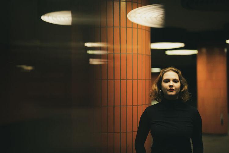Portrait of woman standing in illuminated garage