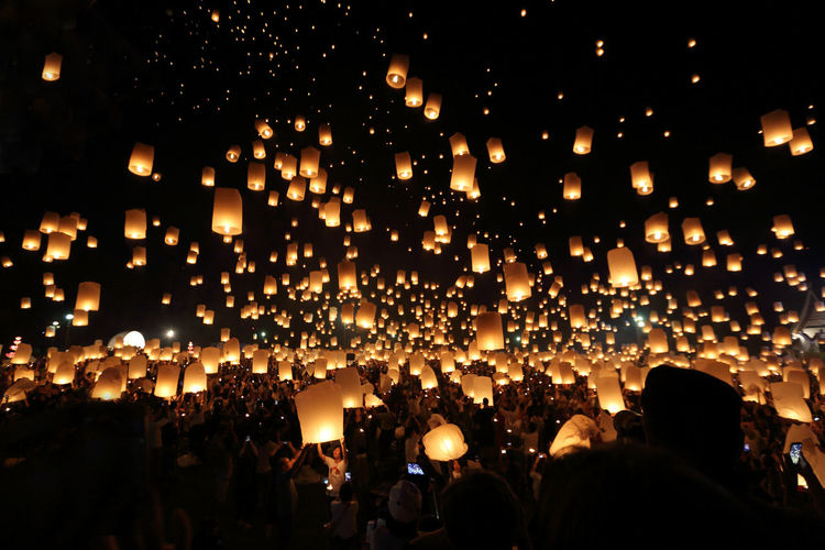 People with illuminated lanterns against sky at night