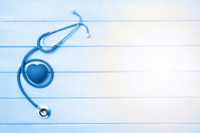 Stethoscope and heart on wooden background. Blue tonned. Table Hear Disease Therapy Health Health Care Stethoscope  Examination Nurse Physician Hospital Medicine Technology Healthy Diagnose Pulse Clinic Reflective Blue Clean Cardiologist Cardiology Doctor  Measurement Instrument Test Reflection Metal Diagnosis Equipment Diagnostic White Heartbeat Emergency Cure Listen Check Heart Device Cardiac Care Treatment Science Desk Tool Exam Closeup Background Medical Indoors  Copy Space Close-up Studio Shot Healthcare And Medicine Still Life No People Medical Equipment Expertise Medical Instrument High Angle View Medical Supplies Group Of Objects Occupation Single Object Full Frame White Color Lab Coat