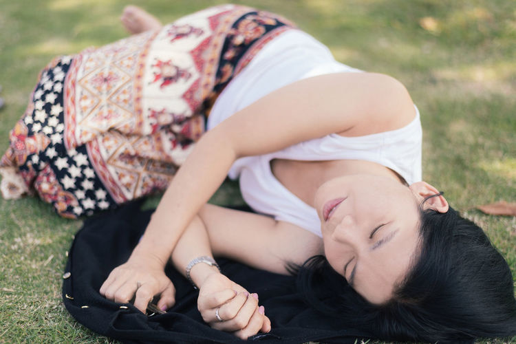 Adult Adults Only Asian Woman Beauty Black Hair Casual Clothing Day Grass Long Hair Lying Lying Down Lying On The Grass One Person One Woman Only One Young Woman Only Only Women Outdoors People Relaxation Sleeping Sleeveless Top Summer Young Adult Young Women