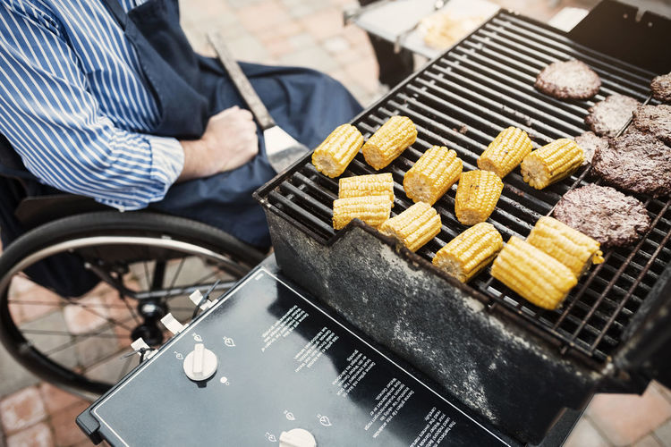 High angle view of man preparing food on barbecue grill