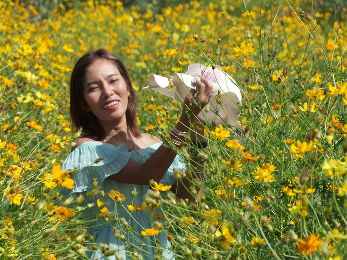 Portrait of smiling young woman with yellow flowers in field