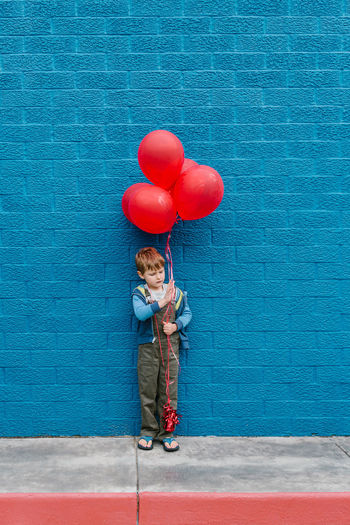 Full Length Of Boy With Red Balloons Standing Against Blue Wall
