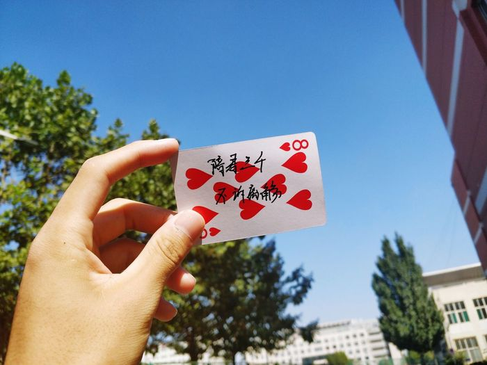 Cropped hand holding card against blue sky