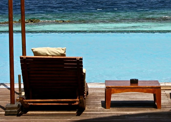 Wooden lounge chair and table by infinity pool
