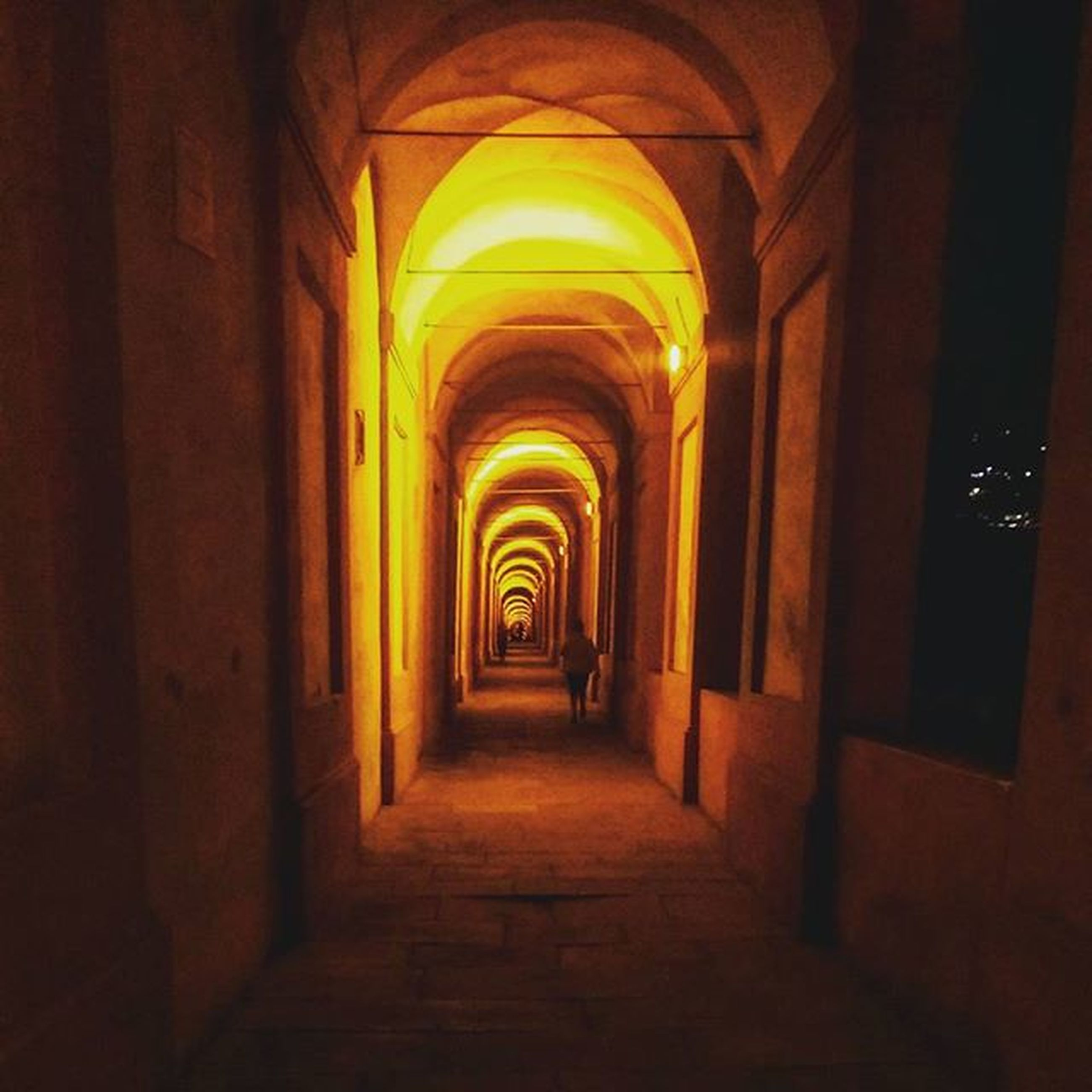 architecture, the way forward, arch, built structure, indoors, corridor, diminishing perspective, illuminated, building, empty, vanishing point, narrow, archway, building exterior, history, night, tunnel, entrance, lighting equipment, walkway