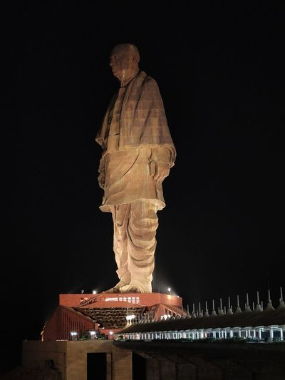 Low angle view of statue against illuminated building against sky at night