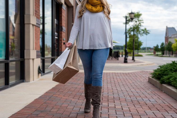 Rear view of woman walking on sidewalk