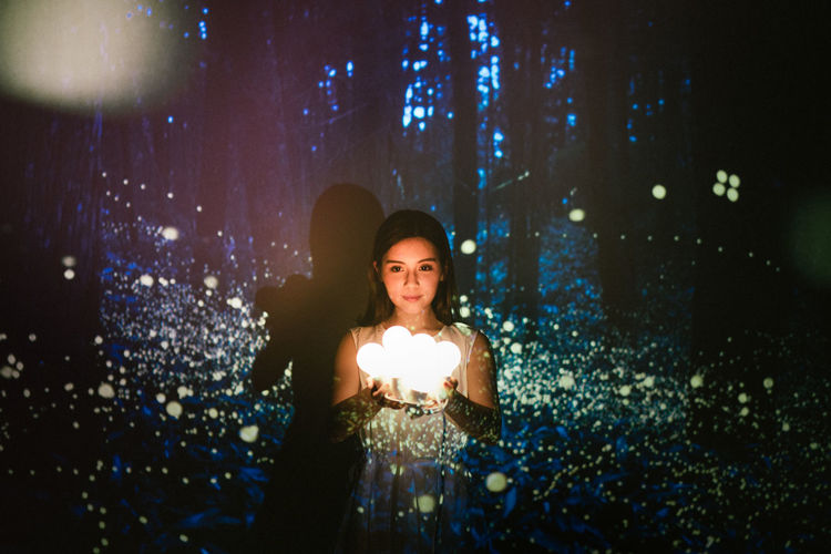 Portrait of happy young woman holding illuminated christmas tree at night