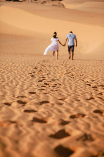 Rear view of couple walking on sand at desert