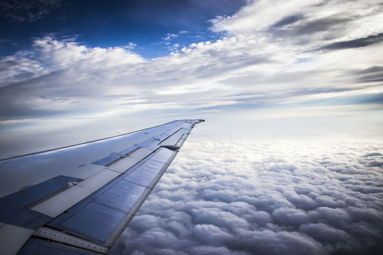 Aerial View Of Airplane Wing Against Cloudy Sky