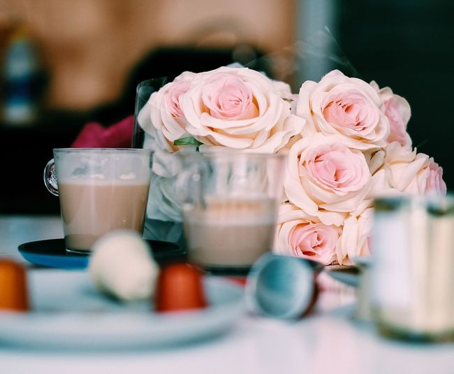 Coffee Cups With Rose Bouquet On Table At Restaurant